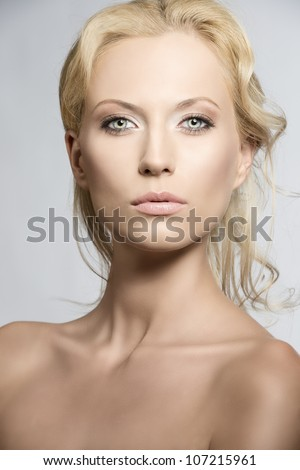 beautiful blonde girl with nudes shoulders and natural makeup, she is in front of the camera and looks in to the lens with sensal expression