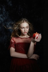 Beautiful blonde girl with pomegranate fruit in her hands. Spring portrait of a girl in a red dress breaking a pomegranate, juice flowing down her hands