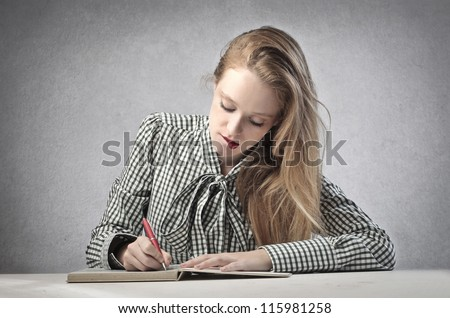 Beautiful blonde girl writing - stock photo