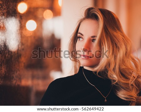 Beautiful blonde girl 20-24 year old sitting in cafe over lights background. Looking away. 20s. Photo stock ©