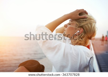 Beautiful blonde hair woman listening to music or radio in headphones while enjoying warm summer evening, pretty hipster girl with closed eyes resting on pier near sea during her long-awaited vacation