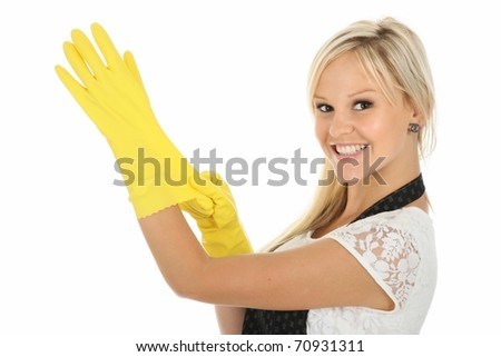 Beautiful blonde housewife putting on yellow latex cleaning gloves