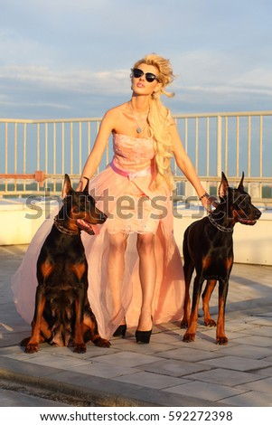 Beautiful blonde in a pink dress and sunglasses with two Doberman on the roof