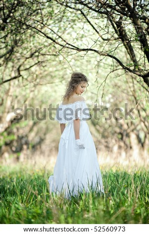 beautiful blonde in white dress walking in forest