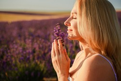 Beautiful blonde is in the field of lavender, holds a bouquet of flowers and enjoys aromatherapy. The girl's eyes are closed. The concept of aromatherapy, lavender oil, photo shoot in lavender