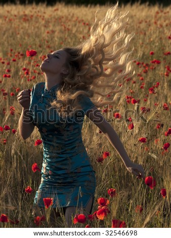Beautiful blonde lady in poppy field shaking hair #32546698
