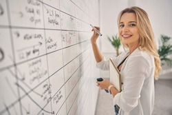Beautiful blonde lady looking at camera and smiling while standing in front of planner whiteboard at work