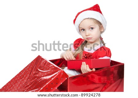 Beautiful blonde little girl dressing in Santa's Helper hat sitting in a Christmas present box over white