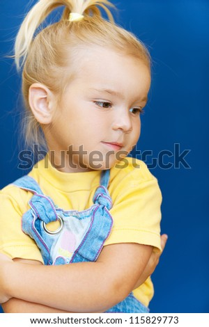 Beautiful blonde little girl was hurt and looks down on blue background.