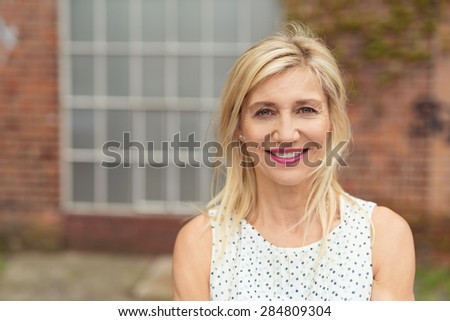 Beautiful blonde middle-aged woman, with medium-length hair and pink lipstick, wearing summer sleeveless dress with dotted pattern while smiling at camera, portrait in front of a building