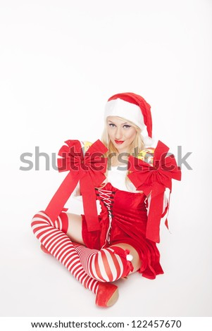 Beautiful blonde model, dressed in a Christmas outfit and holding big red bow decorations, posing on a white background.