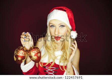 Beautiful blonde model dressed in Christmas outfit holding tree ornaments, on a red background.