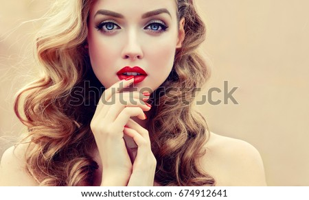 Stock Photo Beautiful  blonde model  girl  with long curly  hair . Hairstyle wavy curls . Red  lips and  nails manicure .  Fashion , beauty and make up portrait