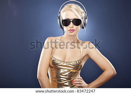 Beautiful blonde model with big headphones, black sunglasses and gold swimwear on a blue background.