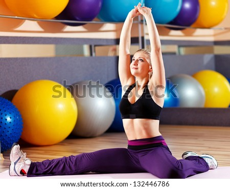 beautiful blonde performs exercises in sports hall