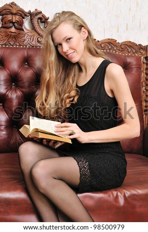 Beautiful blonde reading book. She is sitting on the antique sofa.