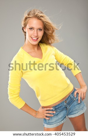 Stock Photo beautiful blonde smiling girl with yellow t-shirt isoated on grey