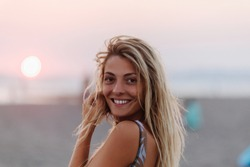 Beautiful blonde smiling woman standing on beach and looking at camera.
