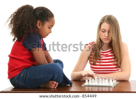 Beautiful blonde teen and adorable preteen playing a game of chess.