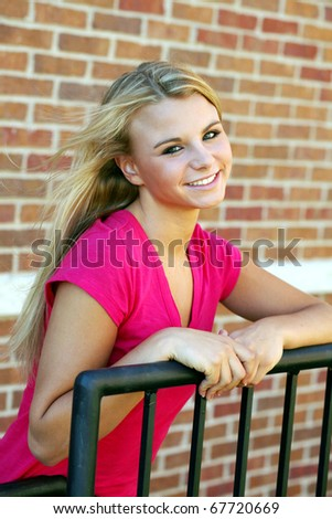 stock photo : beautiful blonde teen girl by brick wall