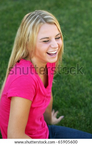 stock photo : beautiful blonde teen girl laughing in grass