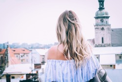 beautiful blonde travel and walks around the city in white dress and with a backpack, looking for a route to the mobile phone via the application