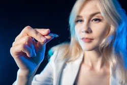 Beautiful blonde with a stylus in her hands. The girl brings the stylus to the glass control panel. Modern technology. Touchscreen. A woman with a stylus in her hands.