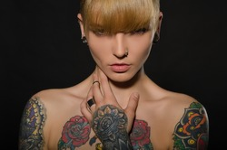 Beautiful blonde with a tattoo on body, dark background