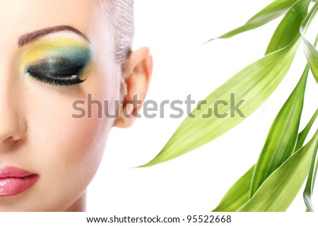 Beautiful blonde with artistic make- up and  bamboo leaves