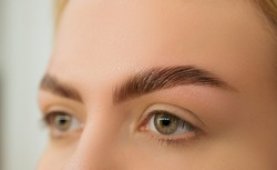 Beautiful blonde with laminated eyebrows. Close-up of laminated and stained eyebrows. Eyebrow Care Trend.  Laminating and Extension for Lashes. Beauty Model with Long Eyelashes and Brows.