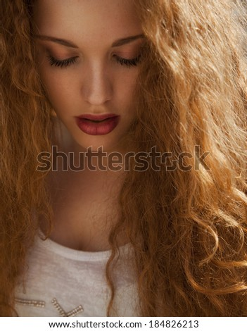 Beautiful Blonde with long curly shine hair and make up. Female with wavy hair and bright make up. vertical shot, studio