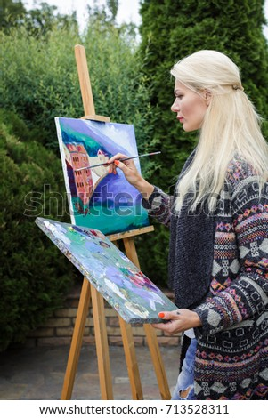 Stock Photo beautiful blonde woman artist with a brush in her hand draws on canvas in the nature.