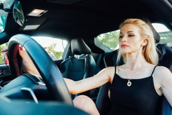 Beautiful blonde woman behind the wheel of car rides