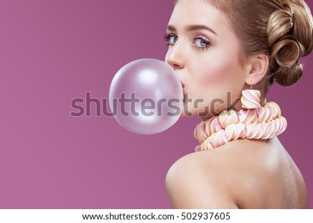 Beautiful blonde woman blowing pink bubble gum. Fashion portrait. #502937605