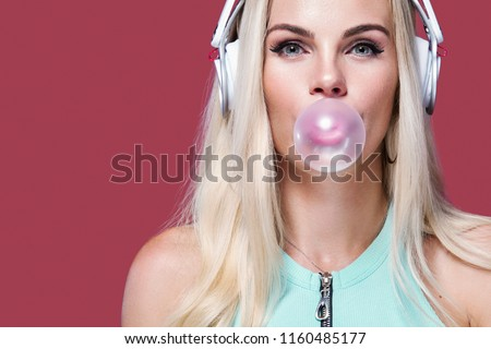 Beautiful blonde woman blowing pink bubble gum. Girl listen music in headphones. Fashion and lifestyle portrait. #1160485177