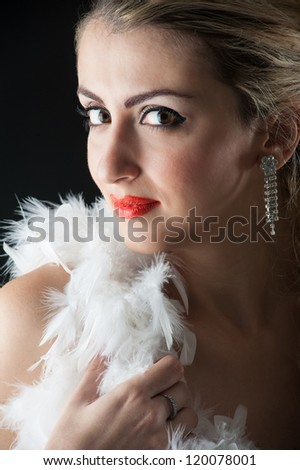 Beautiful blonde woman close up portrait with white ostrich feather against black background.