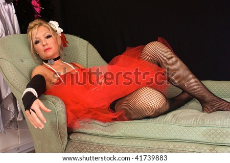 beautiful blonde woman dressed up as old fashioned madam or prostitute, could also be a sexy elf or mrs. claus for christmas, looking directly at viewer.  Shot with blue and red strobes.