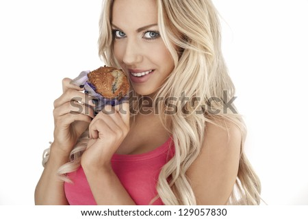Beautiful blonde woman holding a large delicious freshly baked muffin in her hand while smiling at the camera, head and shoulders portrait isolated on white