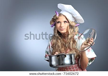 Beautiful blonde woman housewife holding pan. Studio shot over grey background.