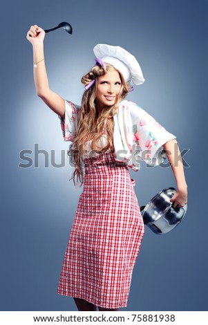 Beautiful blonde woman housewife holding pan. Studio shot over grey background.