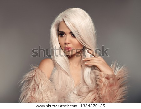 Beautiful Blonde Woman In Faux Fur Coat. Portrait Of Young Sexy Blond Model With Beauty Makeup, long white hair style, posing isolated on gray studio background. High Fashion Winter Style. #1384670135