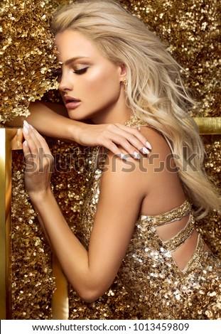Stock Photo Beautiful blonde woman in golden flowers garden