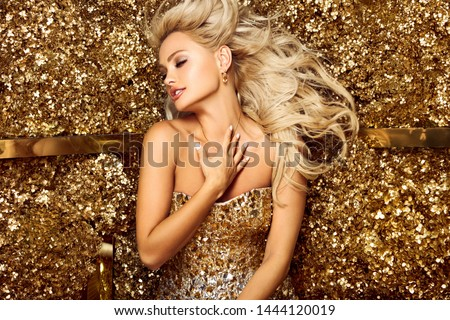 Beautiful blonde woman in golden flowers garden