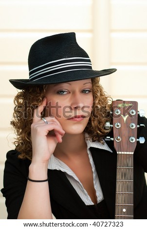 Beautiful blonde woman in hat posing with a guitar