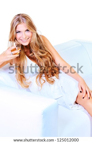 Beautiful blonde woman in light white dress sitting on a sofa. Isolated over white.