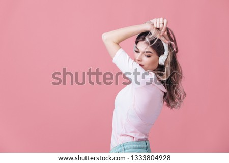 beautiful blonde woman in pink t-shirt and white headphones listens to music on pink background. summer studio photoshoot #1333804928