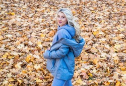beautiful blonde woman in puffer coat. autumn fashion and beauty. pretty girl has long curly blond hair. lady in fall padded jacket in autumn forest. fallen leaves. nature beauty