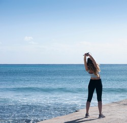Beautiful blonde woman in sportswear stretching her arms on the beach standing in front of the Caribbean Ocean
