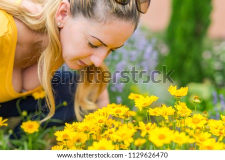 Beautiful blonde woman in yellow top smelling summer flowers in a garden background #1129626470