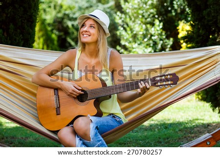 Beautiful blonde woman is sitting on hammock and playing her guitar.Playing guitar